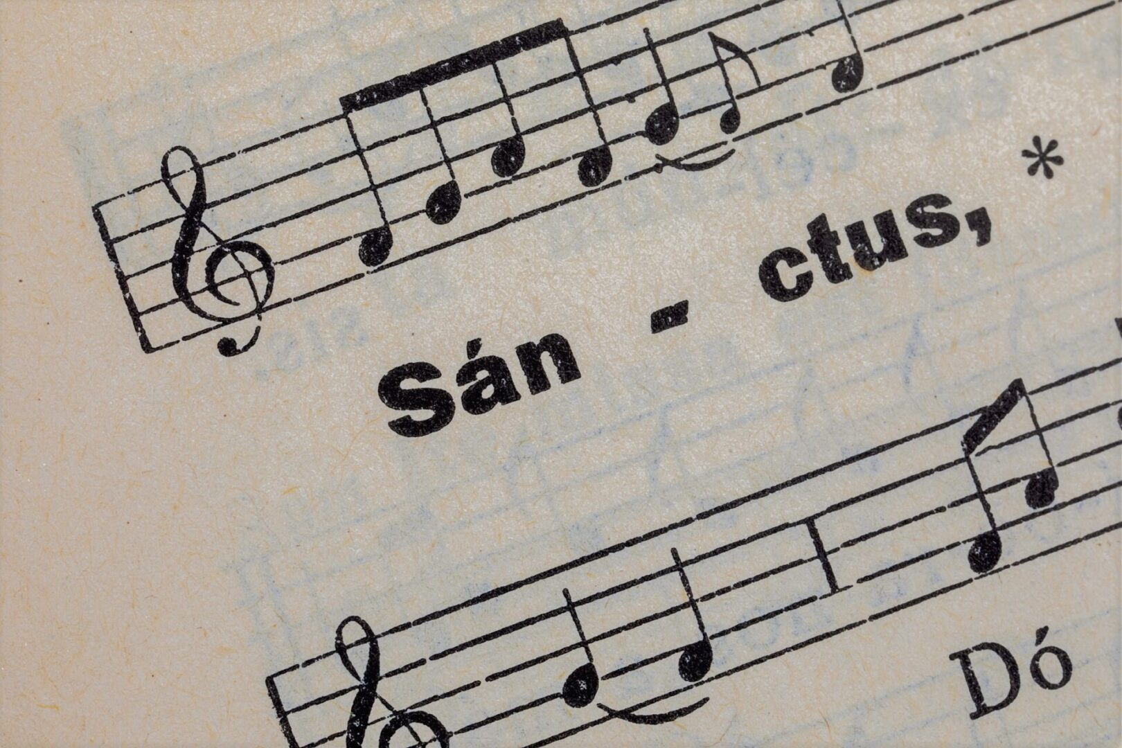 printed word sanctus on the page of an ancient hymnal with staves and musical notes